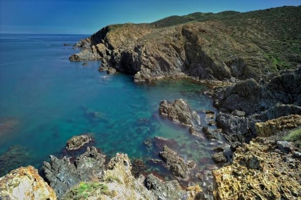 La Côte vermeille offre, au détour du sentier du littoral, de somptueuses criques où l'eau joue la carte de la transparence. Ce littoral aride, où la vigne est la seule à contester la primauté des landes odorantes sur ces sols de schiste, peut rappeler les Cyclades ou certaines parties de la Dalmatie. Au fond, le cap l'Abeille, intégré à la réserve naturelle marine de Cerbère-Banyuls. La première réserve marine française, créée en 1974 et qui s'étend sur 6,5 km et 2 km vers le large, couvrant 650 hectares de mer entre Banyuls-sur-Mer et Cerbère.